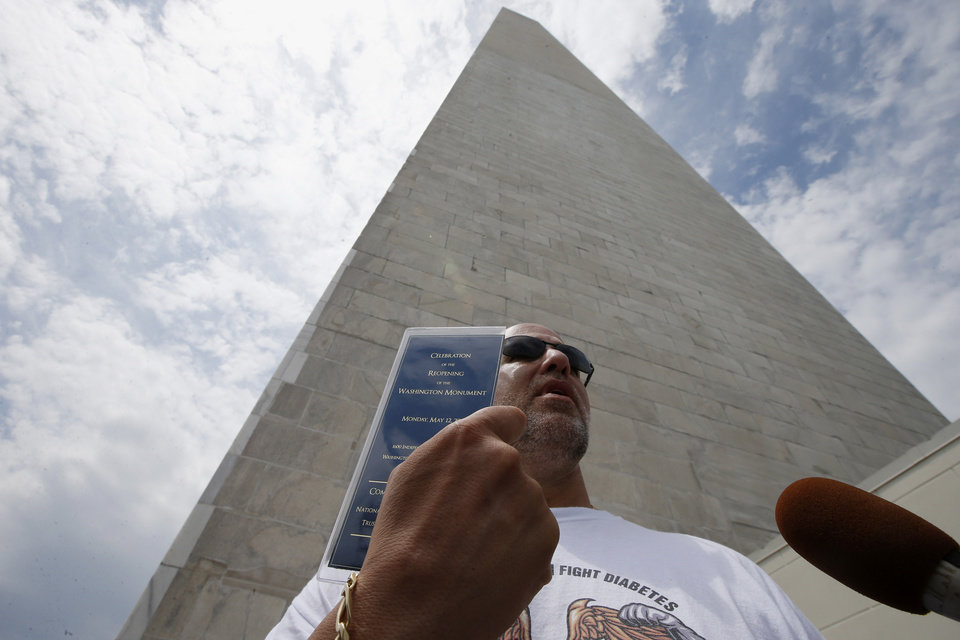 Photo - Marc Tanner, from Boca Raton, Fla., who was in the first group of tourists to visit the newly reopened Washington Monument, holds up a commemorative ticket to celebrate its re-opening, as he is interviewed by reporters after emerging from the monument, Monday, May 12, 2014, in Washington. The monument, which sustained damage from an earthquake in August 2011, reopened to the public today. (AP Photo)