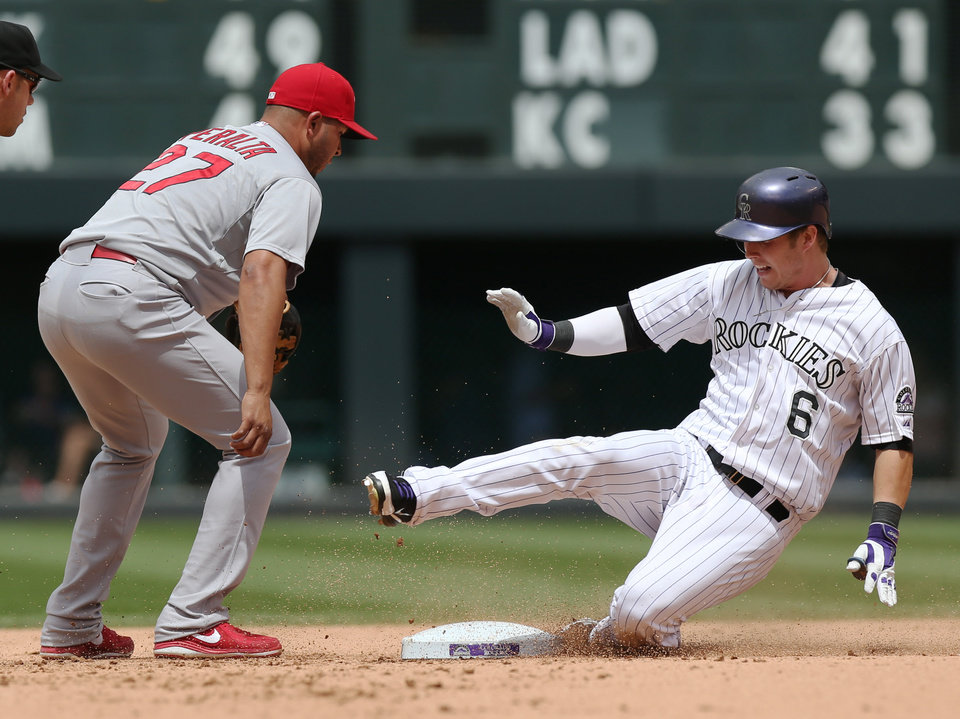 Photo - St. Louis Cardinals shortstop Johnny Peralta, left, turns to apply tag as Colorado Rockies' Corey Dickerson slides safely into second base with a double in the fourth inning of a baseball game in Denver on Wednesday, June 25, 2014. (AP Photo/David Zalubowski)