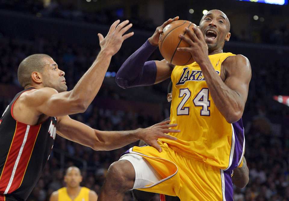 Los Angeles Lakers guard Kobe Bryant, right, goes up for a pass as Miami Heat forward Shane Battier defends during the first half of their NBA basketball game on Thursday, Jan. 17, 2013, in Los Angeles. (AP Photo/Mark J. Terrill)