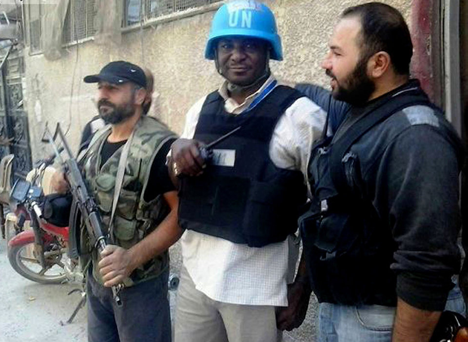 Photo - In this citizen journalism image provided by the United media office of Arbeen which has been authenticated based on its contents and other AP reporting, a member of UN investigation team, is escorted by Syrian rebels, in Damascus countryside of Zamalka, Syria, Wednesday, Aug. 28, 2013. U.N. chemical weapons experts headed to a Damascus suburb on Wednesday for a new tour of areas struck by a purported poison gas attack, activists said, as Western powers laid the groundwork for a possible punitive strike and the U.N. chief pleaded for more time for diplomacy. (AP Photo/United media office of Arbeen)