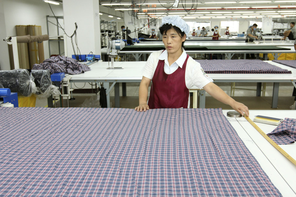 In this Sept. 21, 2012 photo, a North Korean worker prepares to measure fabric at the South Korean-run ShinWon Corp. garment factory inside the Kaesong industrial complex in Kaesong, North Korea. On Wednesday, April 3, 2013, North Korea refused entry to South Koreans trying to cross the Demilitarized Zone to get to their jobs managing factories in the North Korean city of Kaesong. Pyongyang had threatened in recent days to close the border in anger over South Korea's support of U.N. sanctions punishing North Korea for conducting a nuclear test in February. (AP Photo/Jean H. Lee)
