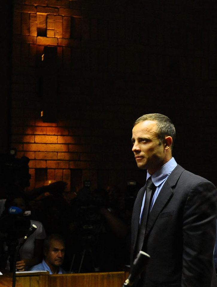 Photo - Olympic athlete Oscar Pistorius stands in court following his bail hearing in Pretoria, South Africa, Tuesday, Feb. 19, 2013.  Pistorius fired into the door of a small bathroom where his girlfriend was cowering after a shouting match on Valentine's Day, hitting her three times, a South African prosecutor said Tuesday as he accused the sports icon of premeditated murder.  The magistrate ruled that Pistorius faces the harshest bail requirements available in South African law, but did not elaborate before a break was called in the session. (AP Photo)
