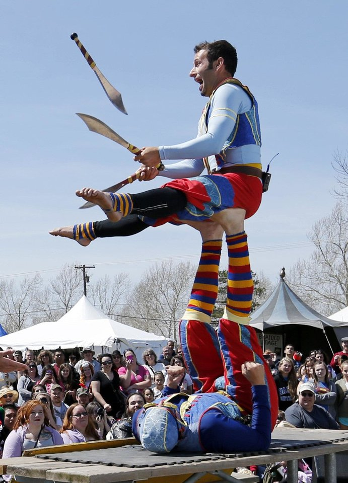 Cameron Tomele juggles perched atop James Freer's feet Friday during a performance by Barely Balanced at 37th annual Medieval Fair at Reaves Park in Norman. The event continues through Sunday. Photos by Steve Sisney,  The Oklahoman