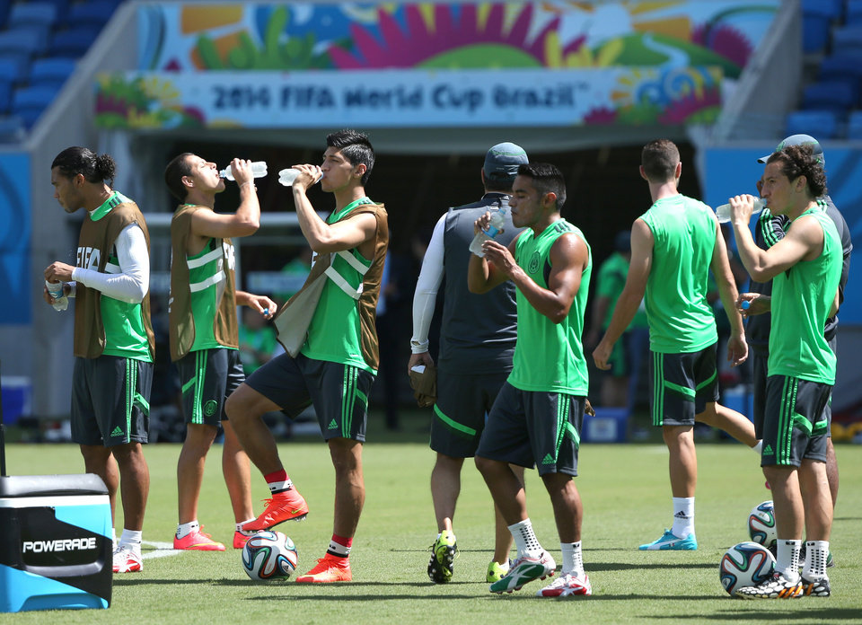Photo - Mexico's soccer players drink water at a training session for the World Cup at the Arena das Dunas stadium in Natal, Brazil, Thursday, June 12, 2014. (AP Photo/Sergei Grits)