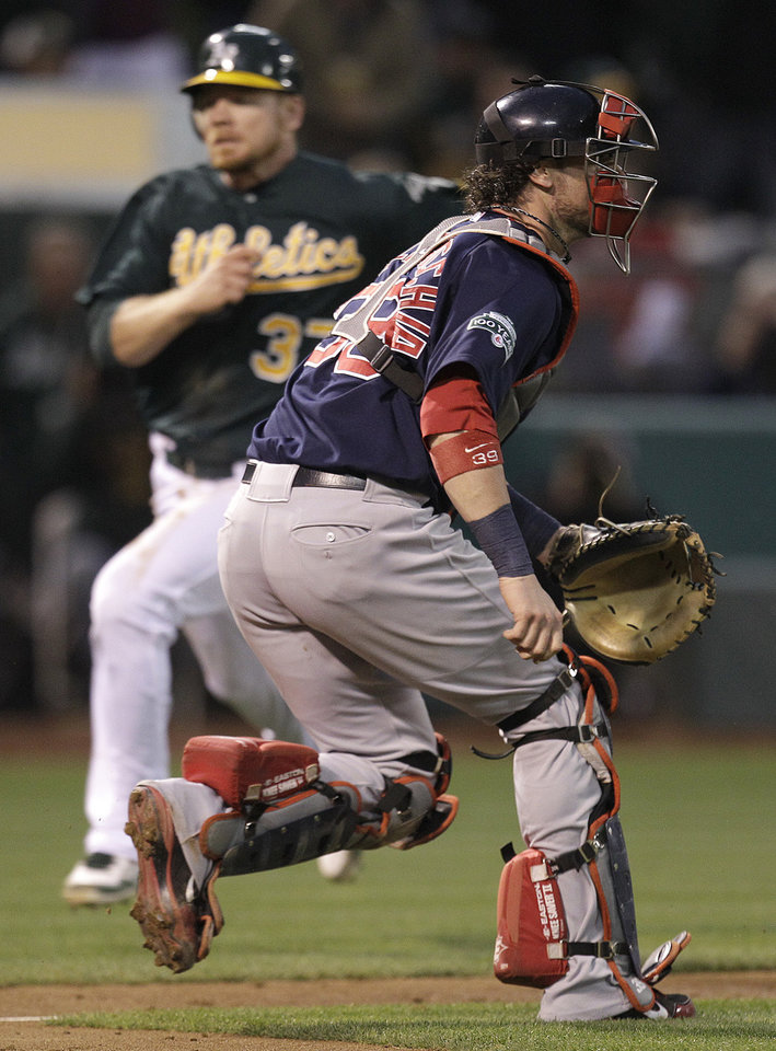 Photo -   Oakland Athletics' Brandon Moss, left, runs to score as Boston Red Sox catcher Jarrod Saltalamacchia waits for the ball in the second inning of a baseball game Friday, Aug. 31, 2012, in Oakland, Calif. Moss scored on a single by A's Jonny Gomes. (AP Photo/Ben Margot)