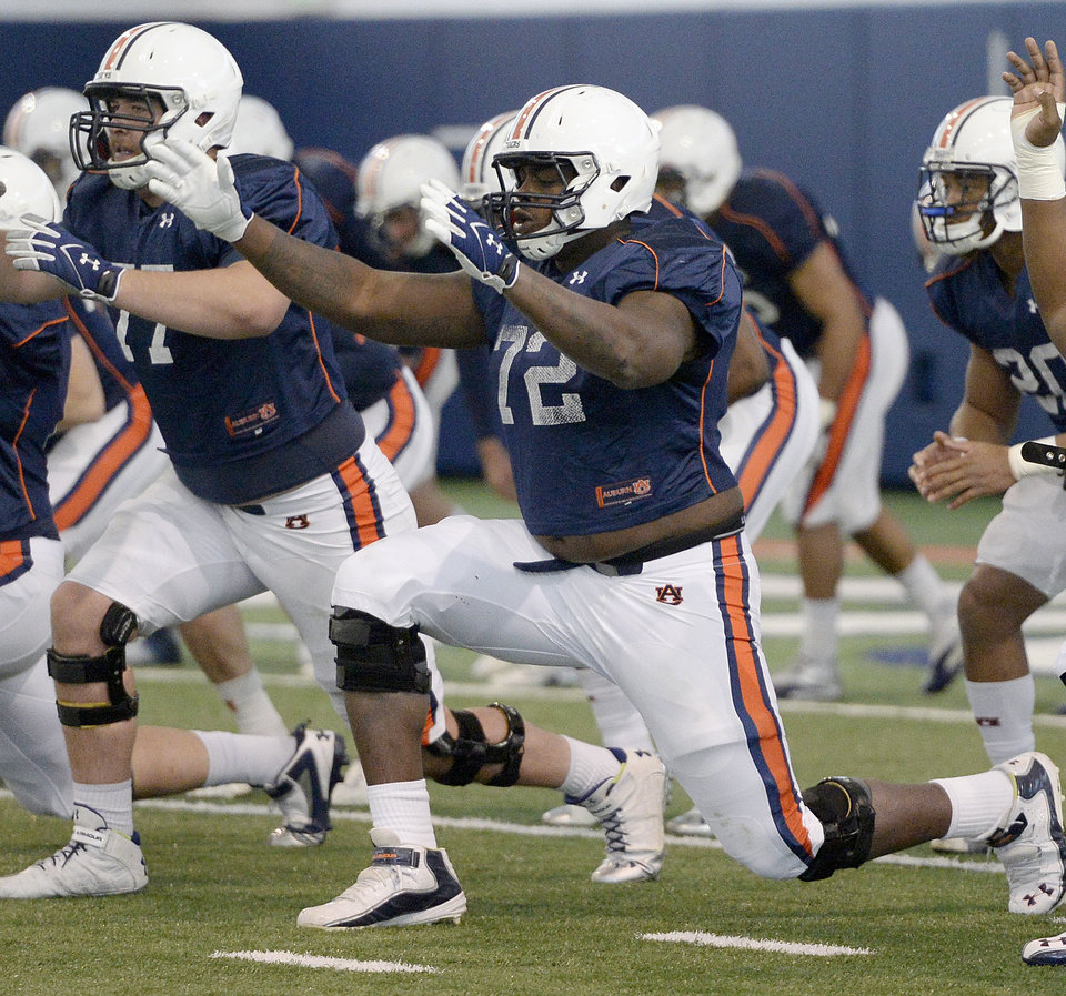 Photo - In this March 25, 2014 photo, Auburn offensive linemen Shane Callahan (77) and Shon Coleman (72) stretch during an NCAA college spring football practice at the Auburn Athletic Complex in Auburn, Ala.  Coleman is battling to replace Greg Robinson as the starting left tackle a few years after overcoming a much tougher fight against cancer. (AP Photo/AL.com, Julie Bennett)
