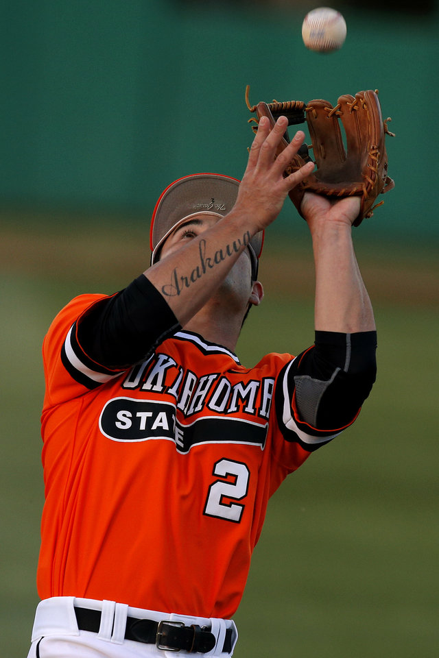 Photo - OSU's Tim Arakawa catches the ball for an out in the third inning of a Bedlam baseball game between Oklahoma State University and the University of Oklahoma in Stillwater, Okla.,Tuesday, April 15, 2014. Photo by Bryan Terry, The Oklahoman