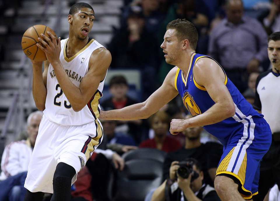 Photo - New Orleans Pelicans power forward Anthony Davis (23) drives against Golden State Warriors power forward David Lee during the first half of the NBA basketball game in New Orleans, Saturday, Jan. 18, 2014. (AP Photo/Jonathan Bachman)