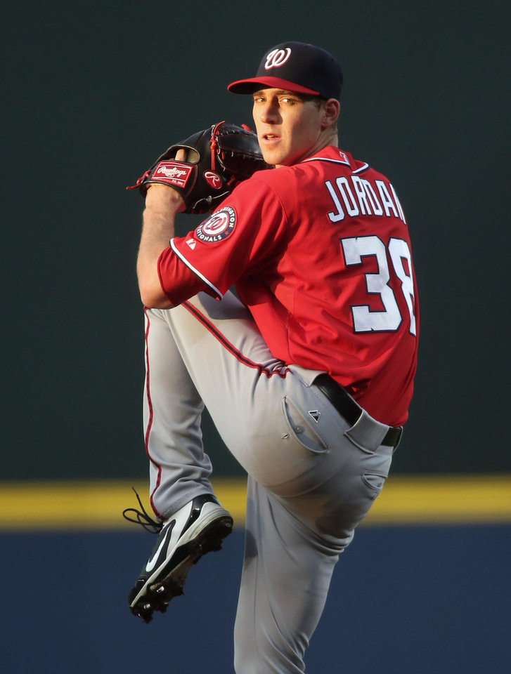 Photo - Washington Nationals starting pitcher Taylor Jordan prepares to deliver to an Atlanta Braves batter in the first inning of a baseball game on Saturday, April 12, 2014, in Atlanta. (AP Photo/Jason Getz)