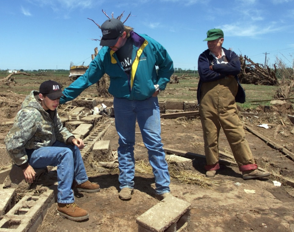 Tornado victims, damage: Kevin Harrison (center) and his father-in-law Laddie Fuksa examine all that remains of a two story frame house in Dover.  Kevin owned two houses next to each other that vanished as he and his family took shelter in a storm cellar.  The shelter caved in on the family which included son Colton, thirteen, left.