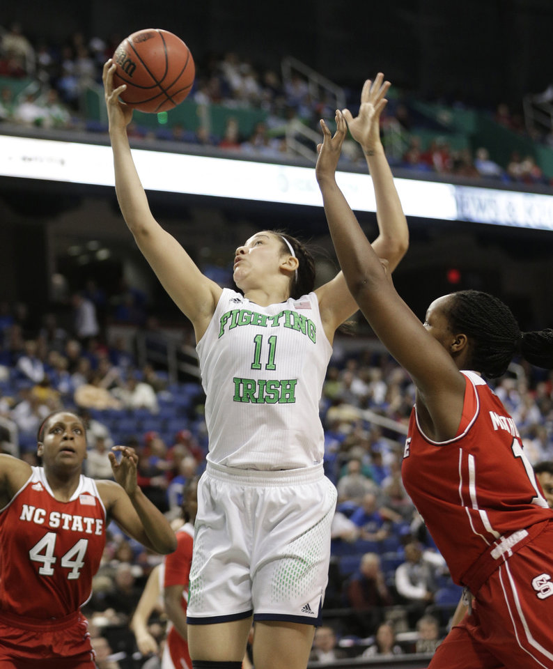 Photo - Notre Dame's Natalie Achonwa, center, shoots as North Carolina State's Jennifer Mathurin, right, and Kody Burke, left, defend during the second half of an NCAA college basketball semifinal game at the Atlantic Coast Conference tournament in Greensboro, N.C., Saturday, March 8, 2014. Notre Dame won 83-48. (AP Photo/Chuck Burton)