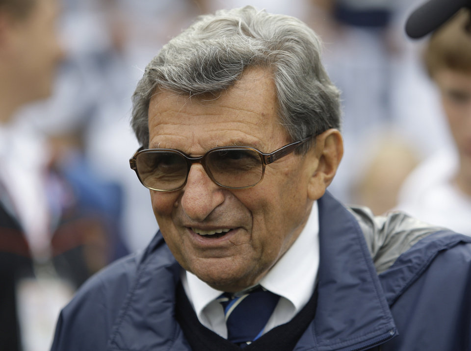 Photo - FILE - In this Sept. 12, 2009 file photo, Penn State coach Joe Paterno walks the field before their college football game against Syracuse in State College, Pa.   The Hall of Fame coach died of lung cancer on Jan. 22, 2012, at age 85. On Tuesday, Jan. 22, 2013,  exactly a year after his passing _ community residents have organized a vigil at a downtown mural that includes a depiction of Paterno.  (AP Photo/Carolyn Kaster, File)