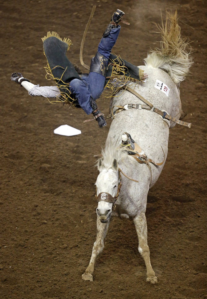 Photo - Timothy Palmer flies off Spring Mills, Pa., as he competes in bareback riding during the National Circuit Finals Rodeo at the State Fair Arena in Oklahoma City, Thursday, April 4, 2013. Photo by Bryan Terry, The Oklahoman