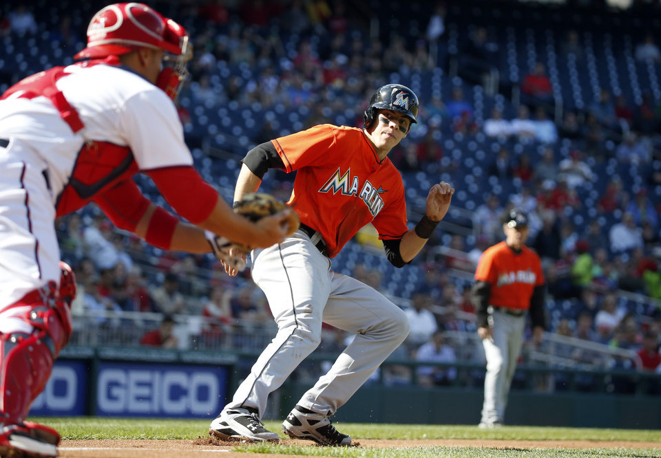 Photo - Miami Marlins' Christian Yelich, center, gets caught in a rundown between home and third base by Washington Nationals catcher Sandy Leon, left, during the  first inning of a baseball game at Nationals Park, Thursday, April 10, 2014, in Washington. Yelich was out on the play (AP Photo/Alex Brandon)