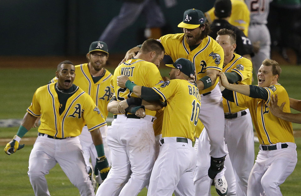 Oakland Athletics' Stephen Vogt, center left, celebrates with teammates after hitting a single off of Detroit Tigers pitcher Rick Porcello to score Yoenis Cespedes during the ninth inning of Game 2 of an American League Division Series in Oakland, Calif., Saturday, Oct. 5, 2013. The Athletics won 1-0. (AP Photo/Jeff Chiu)
