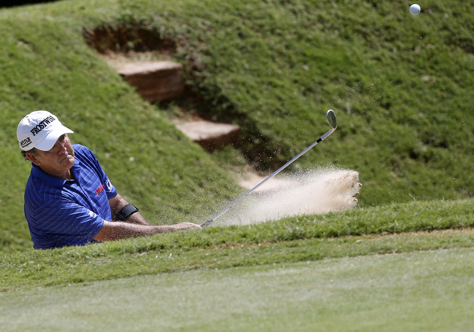 Photo - David Frost hits out of a bunker on the 17th hole in the third round of the U.S. Senior Open golf tournament at Oak Tree National in Edmond, Okla., Saturday, July 12, 2014. Photo by Sarah Phipps, The Oklahoman