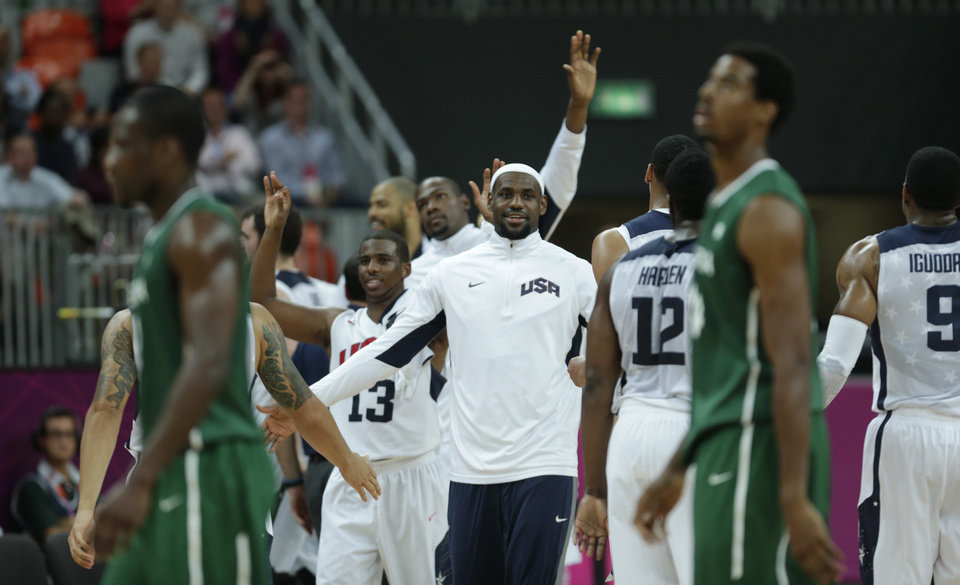Photo -   USA's Lebron James congratulates teammates as Nigerian players walk off the court following a 156-73 win in a men's basketball game at the 2012 Summer Olympics, Thursday, Aug. 2, 2012, in London. (AP Photo/Charles Krupa)