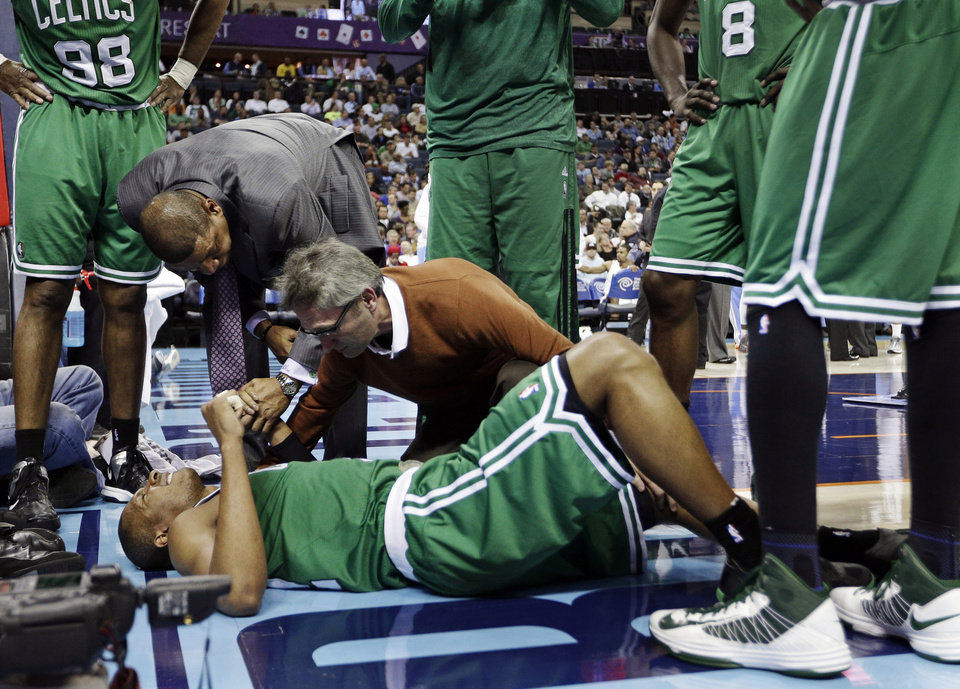 Photo - Boston Celtics head coach Doc Rivers, top left, holds the hand of Leandro Barbosa, bottom, as a trainer examines him during the second half of an NBA basketball game against the Charlotte Bobcats in Charlotte, N.C., Monday, Feb. 11, 2013. Barbosa left the game. The Bobcats won 94-91. (AP Photo/Chuck Burton)