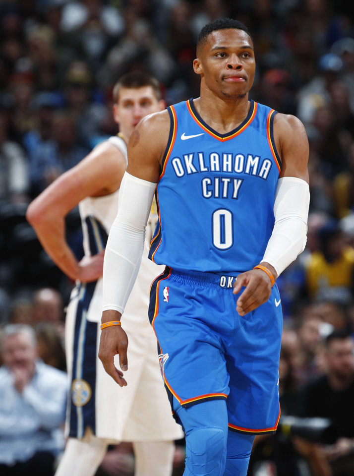 Photo - Oklahoma City Thunder guard Russell Westbrook, front, heads to the bench for attention after getting hit in the face by Denver Nuggets center Nikola Jokic, back, of Serbia, during the first half of an NBA basketball game Thursday, Nov. 9, 2017, in Denver. (AP Photo/David Zalubowski)