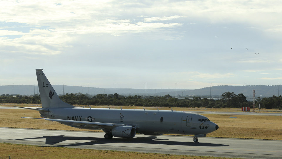 Photo - A U.S. Navy P-8 Poseidon taxies along the runway before it takes off from Perth Airport on route to rejoin the on-going search operations for the missing Malaysia Airlines Flight 370 in Perth, Australia, Thursday, April 10, 2014. Planes and ships hunting for the missing Malaysian jetliner zeroed in on a targeted patch of the Indian Ocean on Thursday, after a navy ship picked up underwater signals that are consistent with a plane's black box. (AP Photo/Rob Griffith)