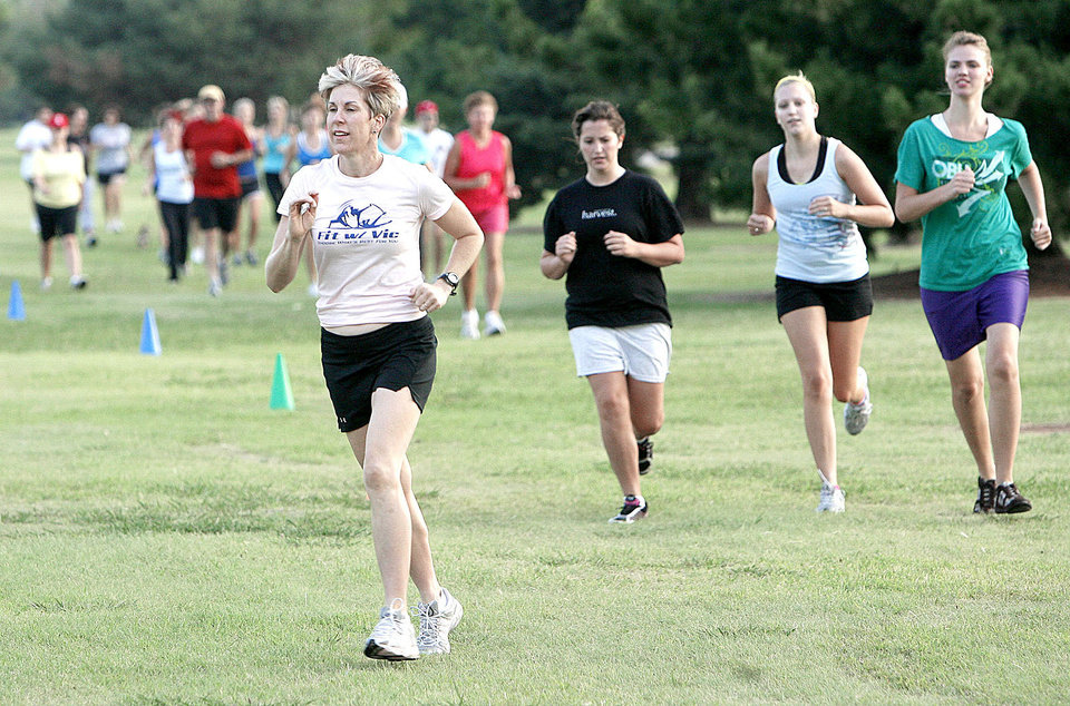 Fitness instructor Vicki Tri leads participants in a free outdoor boot camp exercise class at Earlywine Park in south Oklahoma City. The participants brought dog food to benefit several rescue groups.  PHOTOS BY PAUL HELLSTERN, THE OKLAHOMAN