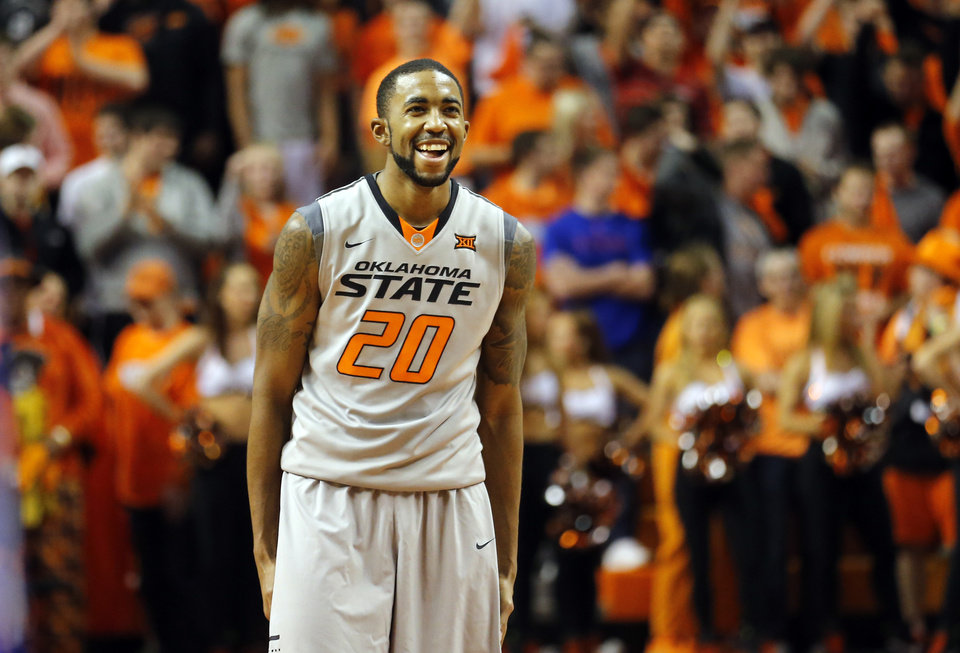 Photo - Oklahoma State's Michael Cobbins (20) celebrates in the final minute of the men's college basketball game between Oklahoma State University and the University of Kansas at Gallagher-Iba Arena in Stillwater, Okla.,  Saturday, Feb. 7, 2015. OSU won 67-62. Photo by Sarah Phipps, The Oklahoman