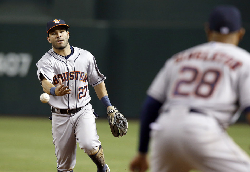 Photo - Houston Astros' Jose Altuve (27) flips the ball to Jon Singleton (28) to get Arizona Diamondbacks' Ender Inciarte out at first base during the third inning of a baseball game on Monday, June 9, 2014, in Phoenix. (AP Photo/Ross D. Franklin)