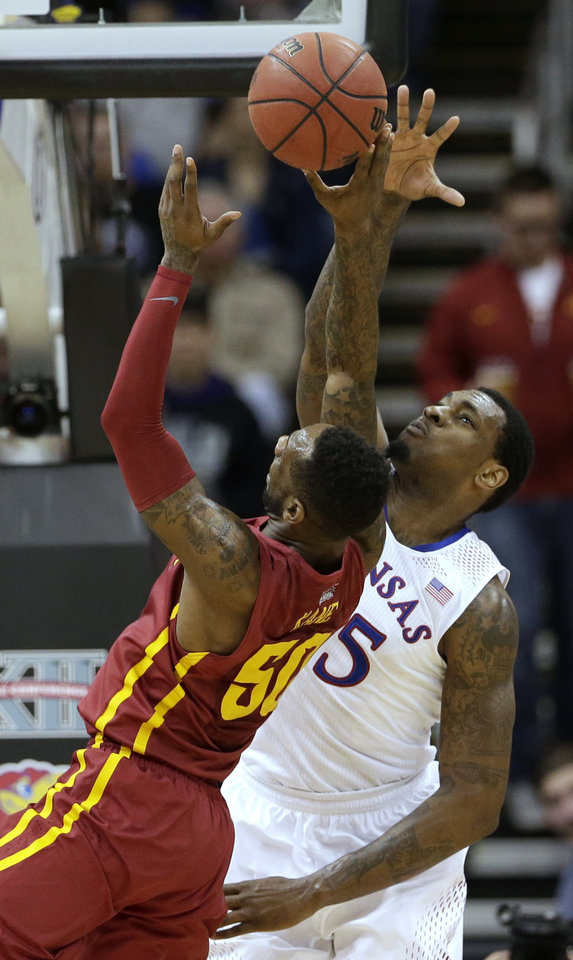 Photo - Kansas' Tarik Black, back, tries to block a shot by Iowa State's DeAndre Kane (50) during the first half of an NCAA college basketball game in the Big 12 men's tournament on Friday, March 14, 2014, in Kansas City, Mo. (AP Photo/Charlie Riedel)