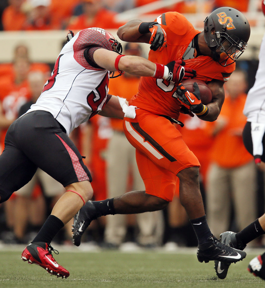 OSU\'s Jeremy Smith (31) runs the ball as ULL\'s Jake Molbert (59) defends in the first quarter during a college football game between Oklahoma State University and the University of Louisiana-Lafayette at Boone Pickens Stadium in Stillwater, Okla., Saturday, Sept. 15, 2012. Photo by Nate Billings, The Oklahoman