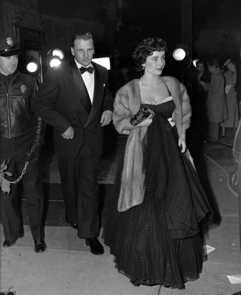 Photo - FILE - In this Dec. 21, 1949, file photo, Elizabeth Taylor arrives for a Hollywood movie premiere with Pittsburgh Pirates' Ralph Kiner, in Los Angeles. The baseball Hall of Fame says slugger Ralph Kiner has died. He was 91. The Hall says Kiner died Thursday, Feb. 6, 2014, at his home in Rancho Mirage, Calif.  (AP Photo/File)