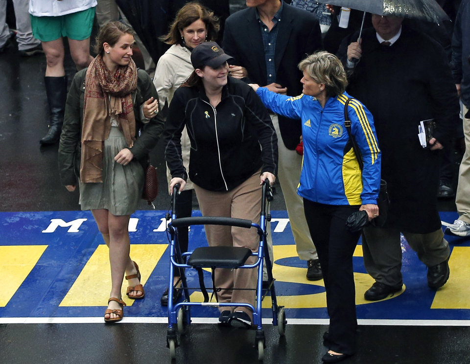Photo - 2013 Boston Marathon bombing survivor Erika Brannock, a pre-school teacher from the Baltimore area, and her mother, Carol Downing, at right, walk across the Marathon finish line after a remembrance ceremony on Boylston Street in Boston, Tuesday, April 15, 2014. (AP Photo/Elise Amendola)