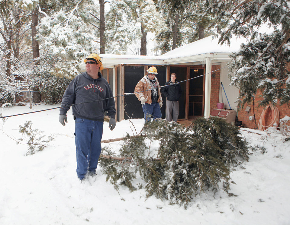 Kelly Taylor, left, and Terry Butler, OG&E workers, on Saturday check Geoffrey Wilson's backyard in Norman. Wilson's power lines were OK, but he lost cable. Photo by Steve Sisney, The Oklahoman