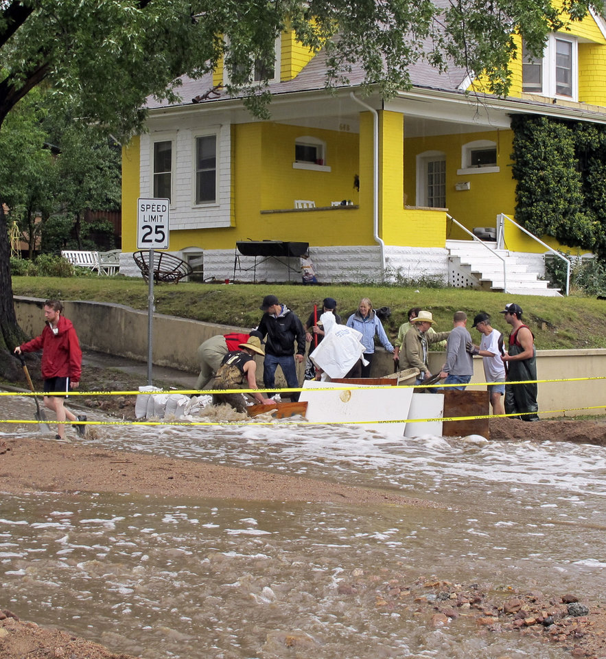 Photo - Residents of a neighborhood on the northern side of Boulder, Colo., work to divert floodwaters away from their homes on Thursday, Sept. 12, 2013. Autorities say flooding in the area has washed out roads, left rural communities isolated and is responsible for at least three deaths. (AP Photo/Ben Neary)