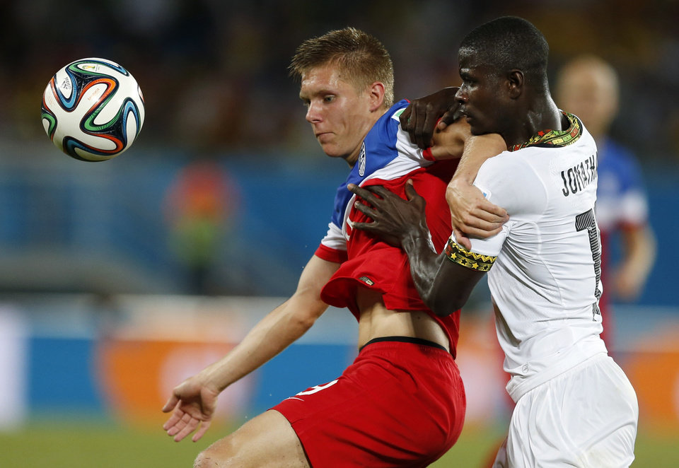Photo - Ghana's Jonathan Mensah, right, tries to push aside United States' Aron Johannsson during the group G World Cup soccer match between Ghana and the United States at the Arena das Dunas in Natal, Brazil, Monday, June 16, 2014. (AP Photo/Julio Cortez)