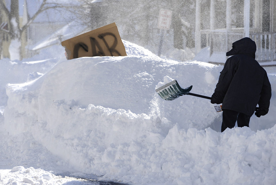 A boy digs around a car marked with a sign on a street in Windsor Locks, Conn., Saturday, Feb. 9, 2013. A behemoth storm packing hurricane-force wind gusts and blizzard conditions swept through the Northeast overnight. (AP Photo/Jessica Hill) ORG XMIT: CTJH108