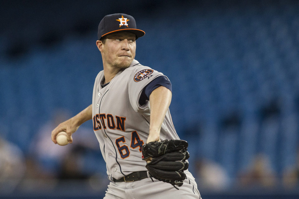 Photo - Houston Astros starting pitcher Lucas Harrell works against Toronto Blue Jays during the first inning of a baseball game Wednesday, April 9, 2014, in Toronto. (AP Photo/The Canadian Press, Chris Young)