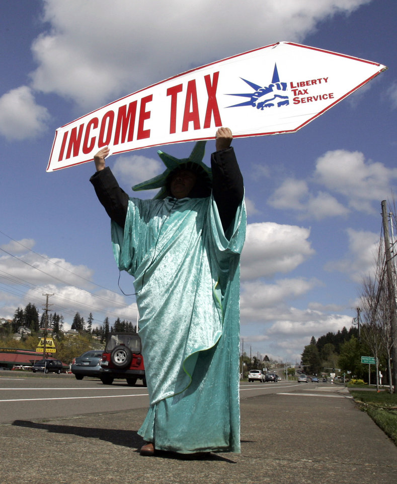 FILE -In this Thursday, April 15, 2010, file photo, Sonia Joaquin holds a sign to remind passing motorists that Thursday is the deadline for taxes in Tigard, Ore. America's decision to re-elect President Barack Obama over Republican presidential candidate, former Massachusetts Gov. Mitt Romney will impact key sectors of the American economy. Upper-income Americans may face a tax increase, while Bush-era tax cuts could be extended for low- and middle-income Americans. (AP Photo/Don Ryan, File)