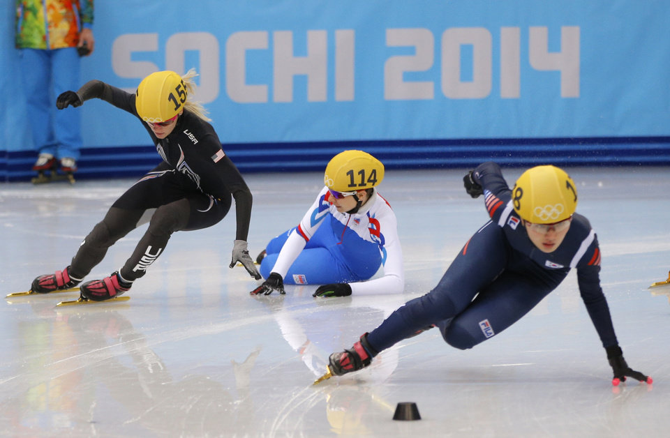 Photo - Katerina Novotna of the Czech Republic, centre, crashes out as she competes with Emily Scott of the United States, left, and Park Seung-hi of South Korea, right, in a women's 1000m short track speedskating heat at the Iceberg Skating Palace during the 2014 Winter Olympics, Tuesday, Feb. 18, 2014, in Sochi, Russia. (AP Photo/Vadim Ghirda)