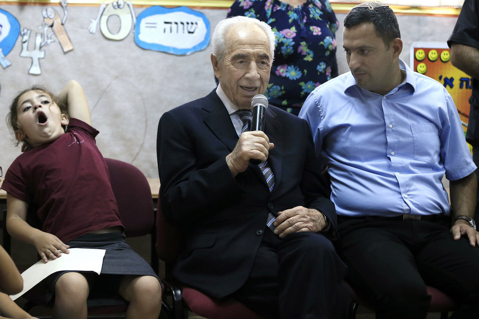 Photo - A girl yawns as Israeli President Shimon Peres talks during a visit to a school in the southern Israeli town of Sderot, Israel, Sunday, July 6, 2014. Peres met local residents enduring the ongoing rocket barrages from neighboring Gaza. (AP Photo/Tsafrir Abayov)