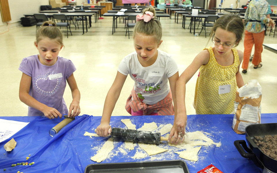 """Photo -  Grace Hanson, 8, Lillian Greene, 10, and Stefi Thanscheidt, 10, roll out dough for a taco recipe at the """"Kids in the Kitchen"""" workshop. Photo by David McDaniel, The Oklahoman   David McDaniel -"""