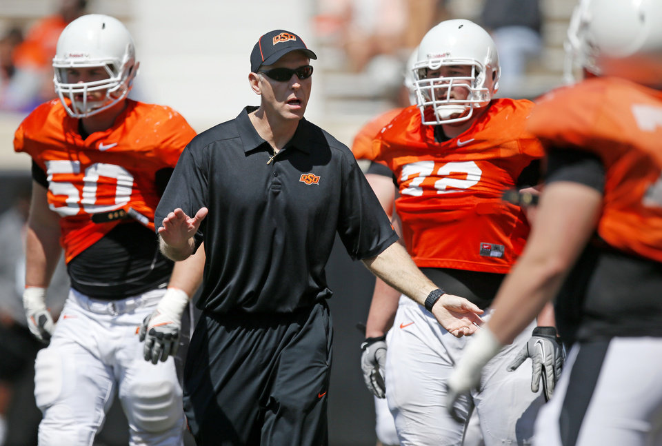 OSU's new offensive line coach Bob Connelly talks with players during Oklahoma State's Orange Blitz football practice at Boone Pickens Stadium in Stillwater, Okla., Saturday, April 5, 2014.