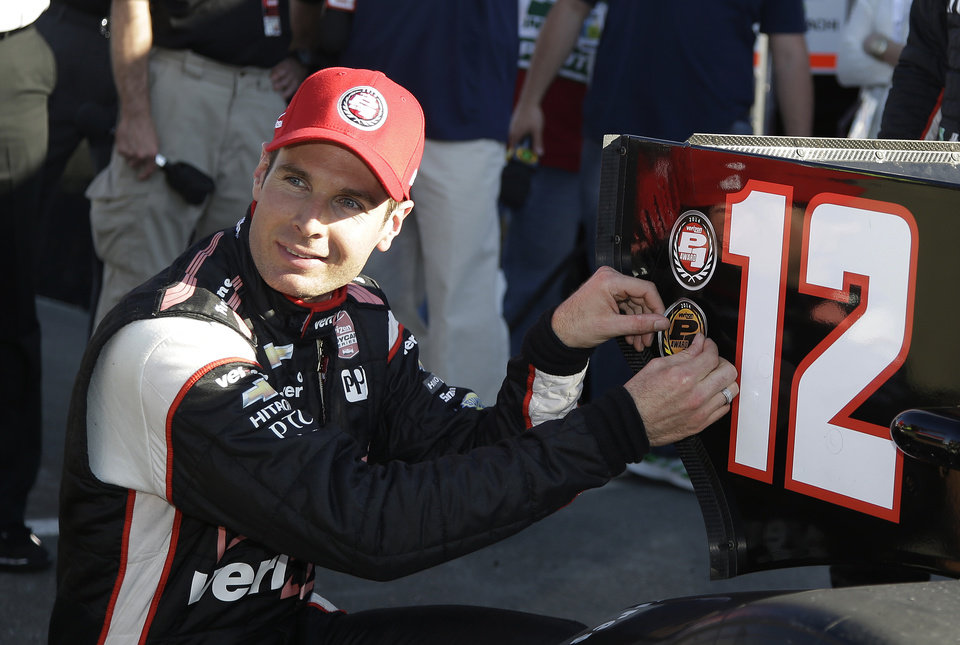 Photo - Will Power of Australia poses placing a sticker on his car after winning the pole position in qualifying for Sunday's IndyCar auto race, Saturday, Aug. 23, 2014, in Sonoma, Calif. (AP Photo/Eric Risberg)
