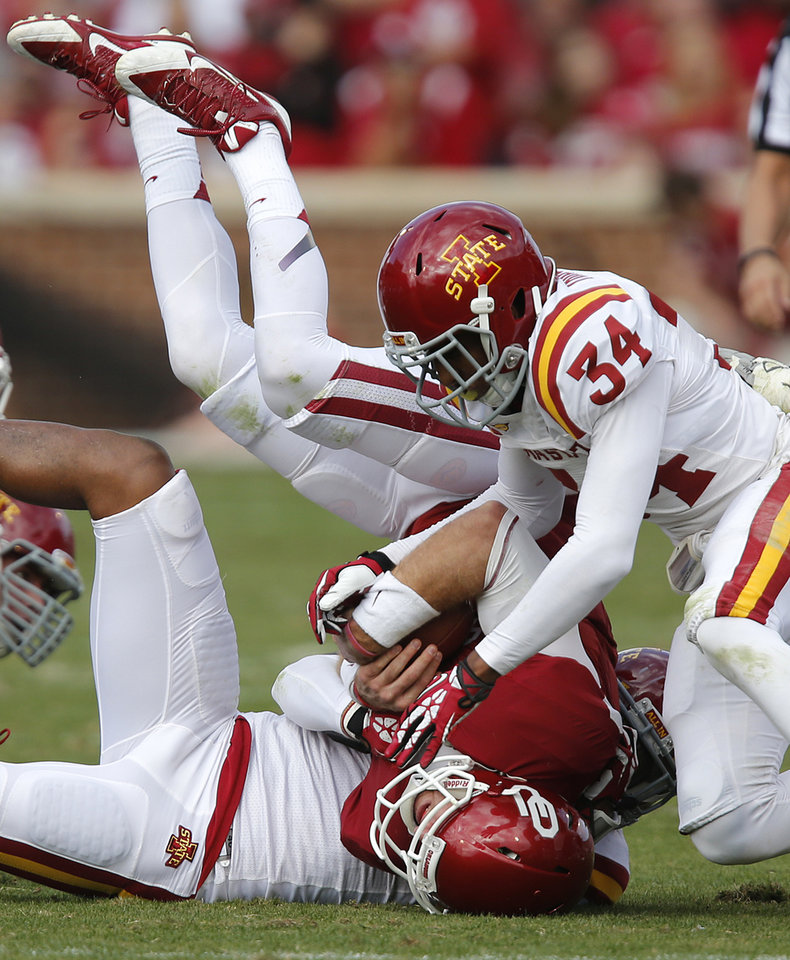 Oklahoma's Trevor Knight (9) is upended by Iowa State's Jacques Washington (5) and Nigel Tribune (34) during the college football game between the University of Oklahoma Sooners (OU) and the Iowa State University Cyclones (ISU) at Gaylord Family-Oklahoma Memorial Stadium in Norman, Okla. on Saturday, Nov. 16, 2013. Photo by Chris Landsberger, The Oklahoman