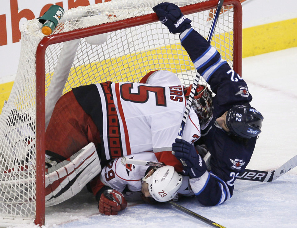 Photo - Winnipeg Jets' Chris Thorburn (22) crashes into Carolina Hurricanes goaltender Justin Peters (35) and Tim Wallace (29) during the first period of their NHL hockey game in Winnipeg, Manitoba, Thursday, April 18, 2013. (AP Photo/The Canadian Press, John Woods)