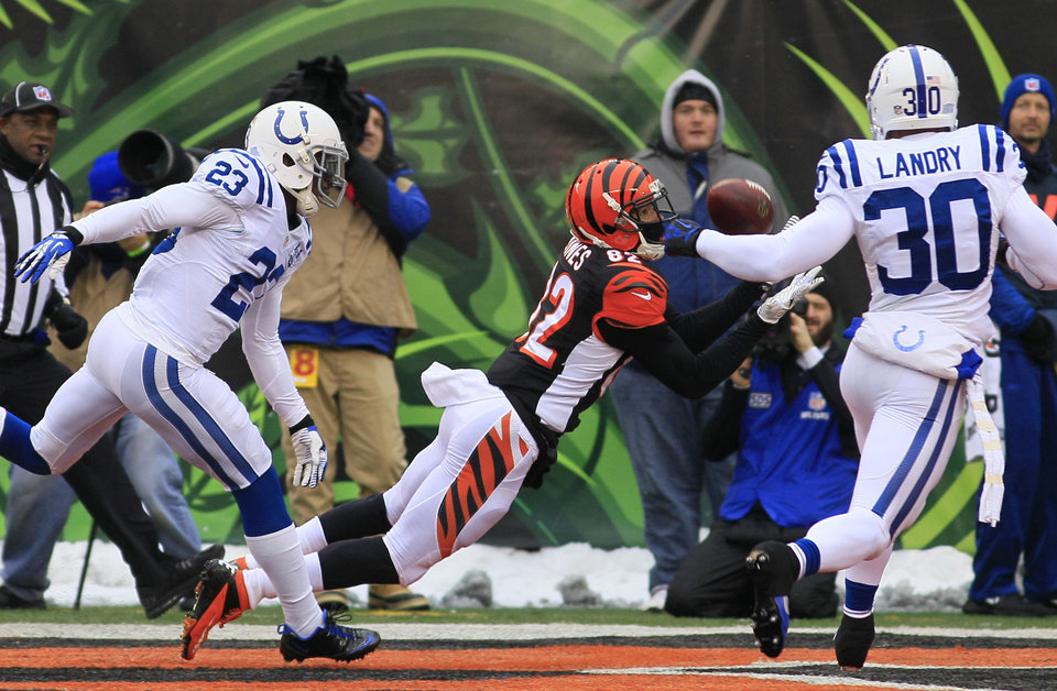 Photo - Cincinnati Bengals wide receiver Marvin Jones (82) catches a 29-yard touchdown pass against Indianapolis Colts cornerback Vontae Davis (23) and strong safety LaRon Landry (30) in the first half of an NFL football game, Sunday, Dec. 8, 2013, in Cincinnati. (AP Photo/Tom Uhlman)