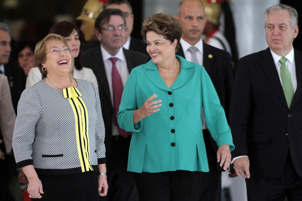 Photo - Brazil's President Dilma Rousseff, right, talks with Chile's President Michelle Bachelet at the Planalto presidential palace in Brasilia, Brazil, Thursday, June 12, 2014. (AP Photo/Eraldo Peres)