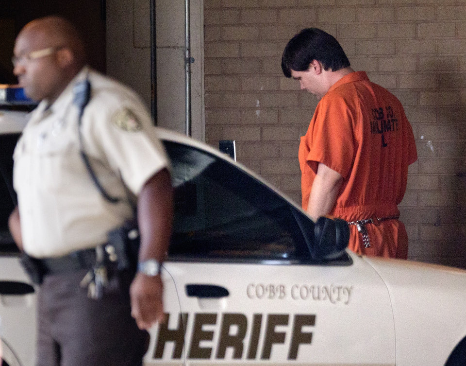 Photo - Justin Ross Harris, right, the father of a toddler who died after police say he was left in a hot car for about seven hours, arrives for his bond hearing at Cobb County Magistrate Court Thursday, July 3, 2014, in Marietta, Ga. Harris is currently being held without bond on a child cruelty charge and a murder charge. (AP Photo/David Goldman)