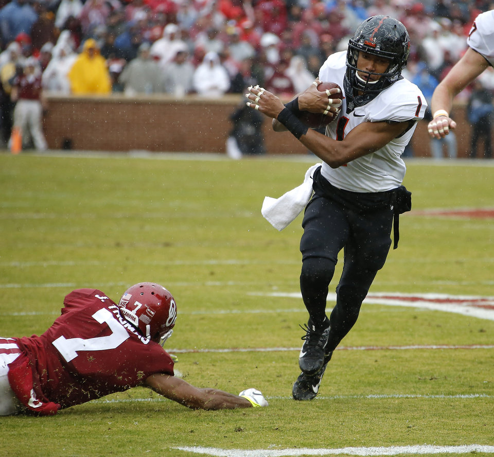 Photo - Oklahoma State's Jalen McCleskey (1) runs past Oklahoma's Jordan Thomas (7) during the Bedlam college football game between the Oklahoma Sooners (OU) and the Oklahoma State Cowboys (OSU) at Gaylord Family - Oklahoma Memorial Stadium in Norman, Okla., Saturday, Dec. 3, 2016. Photo by Bryan Terry, The Oklahoman