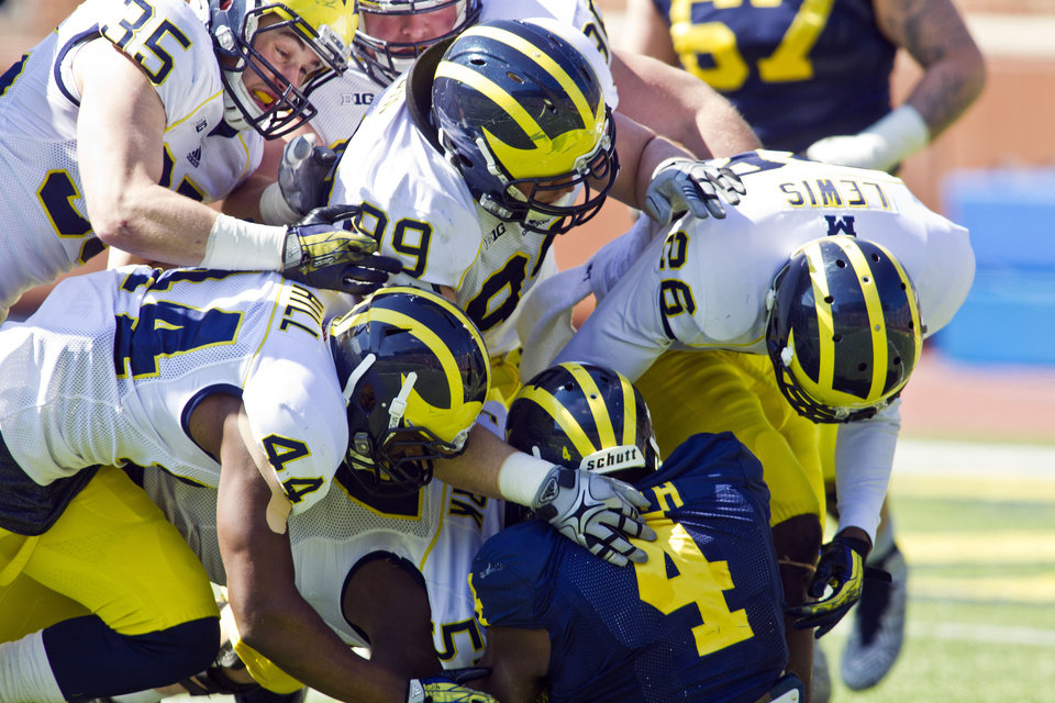 Photo - Michigan running back De'Veon Smith (4) is gang-tackled by linebacker Joe Bolden (35), defensive back Delano Hill (44), defensive tackle Matthew Godin (99) and defensive back Jourdan Lewis (26) during the team's annual spring football game, Saturday, April 5, 2014, in Ann Arbor, Mich. (AP Photo/Tony Ding)