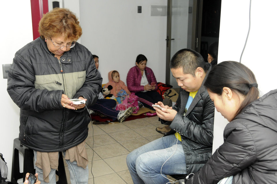 Photo - People use their phones on the upper floor of an apartment building located a few blocks from the coast where they gathered to avoid a possible tsunami after an earthquake in Iquique, Chile, Tuesday, April 1, 2014. A powerful magnitude-8.2 earthquake struck off northern Chile on Tuesday night, setting off a small tsunami that forced evacuations along the country's entire Pacific coast.  (AP Photo/Cristian Viveros) NO PUBLICAR EN CHILE
